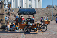 """Helsinki, Finland -- July 19, 2019. A vendor has a food cart set up by the stairs at Tuomiokirkko, the """"Big White Church""""."""