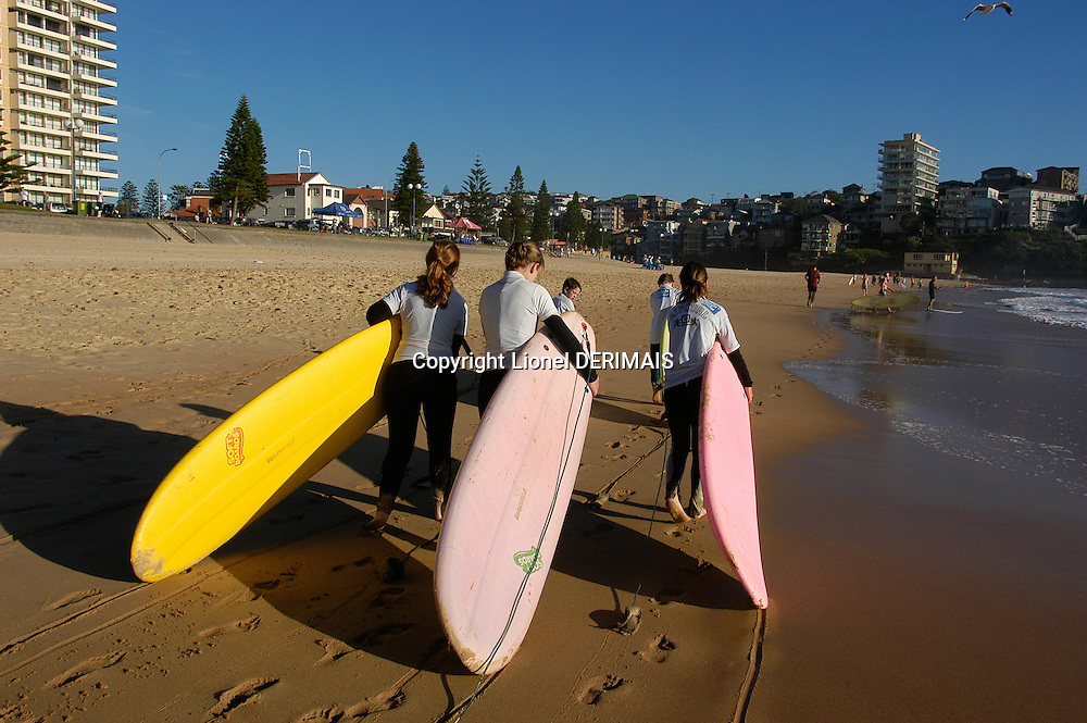 Early morning young women go surfing in Manly beach, Sydney, Australia.