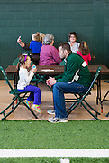 Mark Ferguson watches his daughter Samantha Ferguson take a lick of her snow cone during the Fieldhouse Fest on Sibs Weekend.