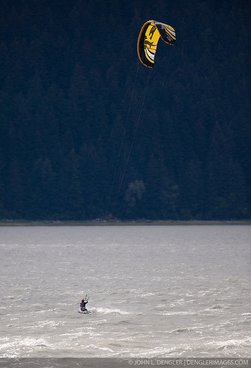 A kiteboarder uses his kite to surf the Chilkat Inlet near Haines, Alaska.