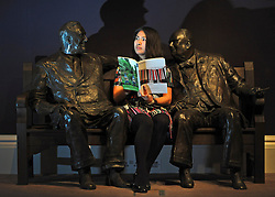 © Licensed to London News Pictures. 11/11/2011. London, UK. A woman reads an auction catalogue whilst sitting on Lawrence Holofcener's The Allies. The sculpture features Sir Winston Churchill talking to Franklin Roosevelt. A cast of this original sits between Old and New Bond Street in central London and was gifted to celebrate 50 years of peace. Sotheby's preview of Modern and Post-War British Art which will offered for sale at auction on 15th November 2011. Photo credit : Stephen Simpson/LNP