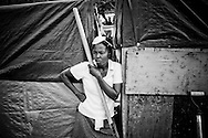 A woman living in a camp for those displaced by the recent earthquake takes a rest while shoveling trash in Petionville, outside Port-au-Prince, Haiti.