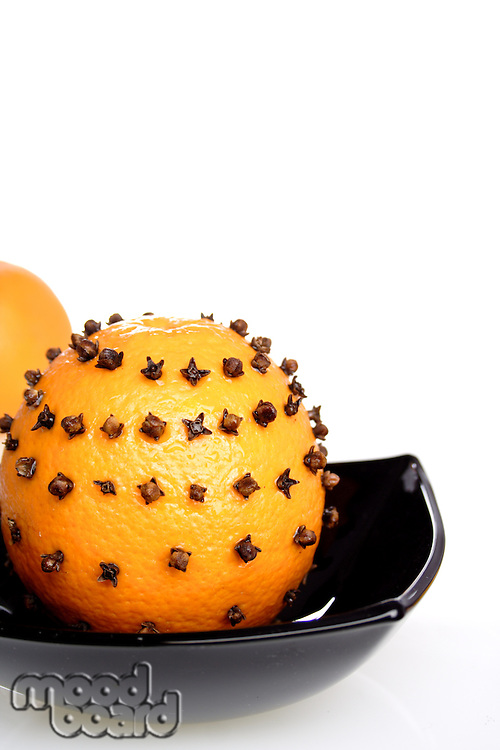 Oranges with cloves on white background