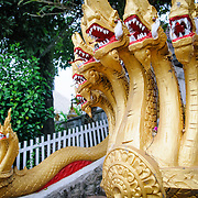 Gold-leaf naga depicting king cobras or sea serpents protect the entrance to Wat Phonxay Sanasongkham in Luang Prabang, Laos. Naga are a common architectural ornament at Lao Buddhist temples.
