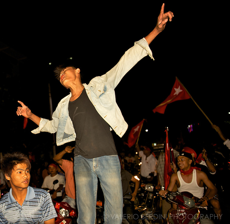 A NLD fan dances on a night parade in Mandalay. Myanmar. 2012