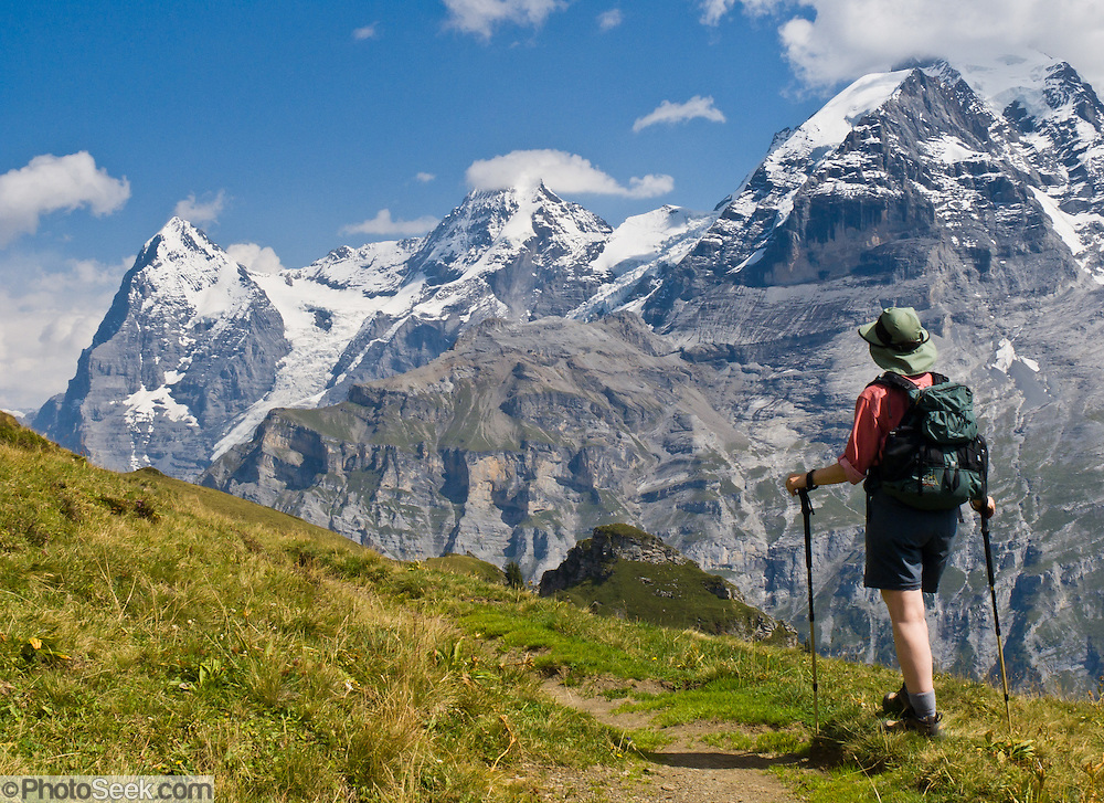 """From Wasenegg Ridge, a hiker sees peaks of Eiger (the Ogre, 13,026 feet), Mönch (the Monk), and Jungfrau (the Virgin, 13,600 feet), in the Berner Oberland, Switzerland, the Alps, Europe. The Bernese Highlands are the upper part of Bern Canton. UNESCO lists """"Swiss Alps Jungfrau-Aletsch"""" as a World Heritage Area (2001, 2007)."""