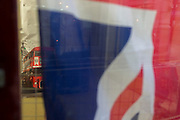 A detail of a red London bus with London landmarks peeping behind a crumpled British Union Jack flag in the window of a City retailer, on 2nd February 2017, in the City of London, England.