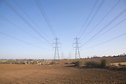 Electricity pylons and transmission lines cross countryside, Claydon, Suffolk, England