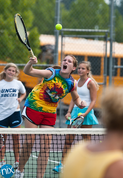 Tennis student Kayla Russell hits an overhead during a tennis camp run by Upchurch Tennis at Jay M. Robinson High School Tuesday morning. (Photo by James Nix)