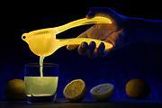 Lemon juice pours from a glowing citrus press. Blacklight photography.