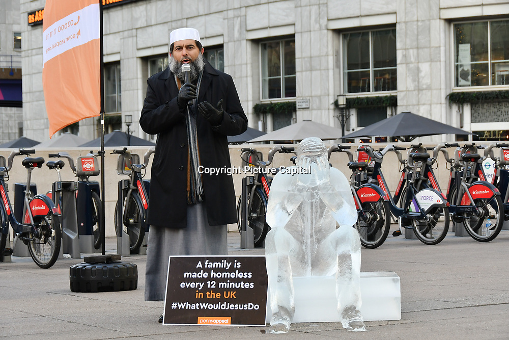 "Speaker Shaykh Ibrahim Mogra at Penny Appeal Team Orange unveiling 5 life-size ice statues ""What Would Jesus Do?"", symbolising homeless families to promote their winter campaign. The frozen family will depict the plight of the 140* families who become homeless everyday, and the 900* children who become homeless every month on 17th December at Canary Wharf, London, UK."