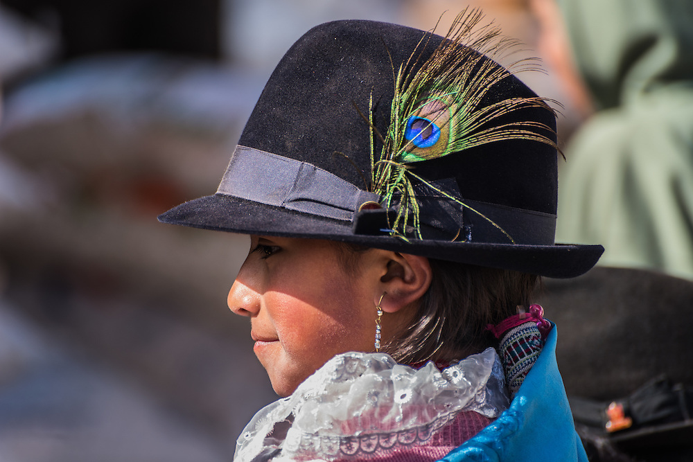 A young girl from the town of Zumbahue with the for this village traditional hat with a peacock feather, Zumbahue, Ecuador.