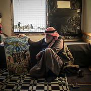 Mahmoud Abu Sbeih, 70, a palestinian refugee who escaped Syria with his family, looks at his painting, on december 20th 2013 in his room of Cyber City.