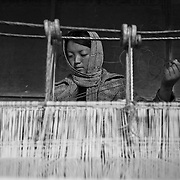 Girl working at a loom weaving a carpet, Bumthang, Bhutan, Asia