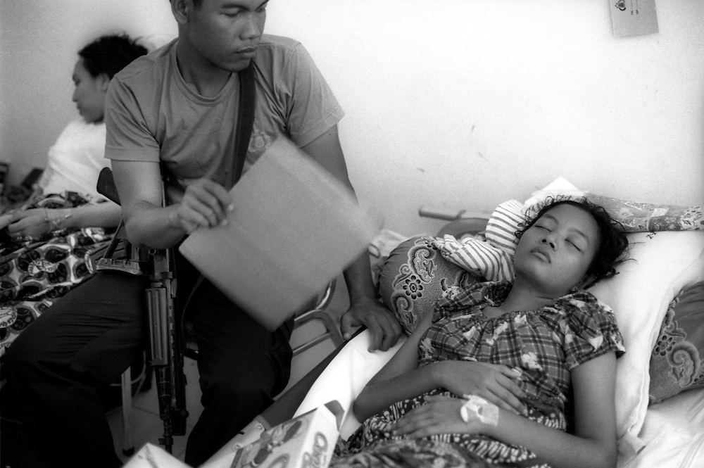 A young Indonesian member of BRIMOB, Julian Intarina comforts his sister Numun at Farkinah Hospiotal in Banda Aceh. 06/01/05