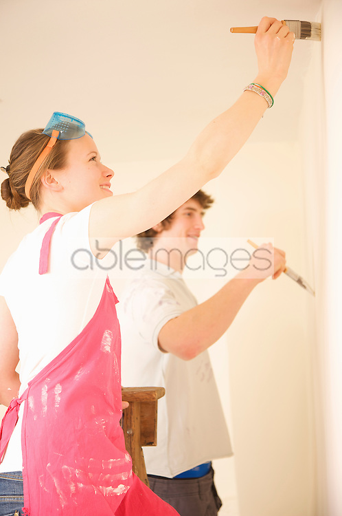 Profile of a young couple painting a white wall
