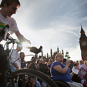 Lisa Egan, former stand-up comedian, now full-time wheel chair bound and poorly after severe illness, speaking in defence of the NHS. The amp and speaker is powered by bicycle..The Health and Care Bill has been passed by Parliament and is due to go to the House of Lords. In protest against the bill which aim to deconstruct and privatise large parts of the NHS UK Uncut activists together with health workers and trade unionists blocked the Westminster Bridge from 1pm til 5.30pm.