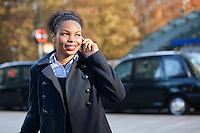 Smiling African American young woman using mobile phone outdoors