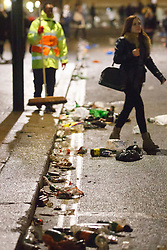 © licensed to London News Pictures. London, UK 01/01/2014. The rubbish left by revellers in Westminster, London being cleaned at the first hours of 2014. Photo credit: Tolga Akmen/LNP