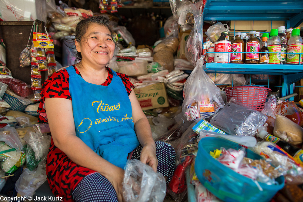 17 JANUARY 2013 - SAMUT SONGKHRAM, SAMUT SONGKHRAM, THAILAND: A market vendor in the Samut Songkhram market. Four trains each day make the round trip from Baan Laem, near Samut Sakhon, to Samut Songkhram, the train chugs through market eight times a day (coming and going). Each time market vendors pick up their merchandise and clear the track for the train, only to set up again when the train passes. The market on the train tracks has become a tourist attraction in this part of Thailand and many tourists stop to see the train on their way to or from the floating market in Damnoen Saduak.    PHOTO BY JACK KURTZ