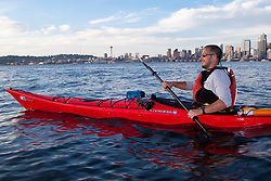 North America, United States, Washington, Seattle, male kayaker with Seattle downtown skyline in distance.  MR