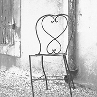 An old chair with ornate iron work outside in the street
