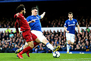 Liverpool defender Virgil van Dijk (4) gets a vital touch to take it away from Liverpool forward Mohamed Salah (11) during the Premier League match between Everton and Liverpool at Goodison Park, Liverpool, England on 3 March 2019.