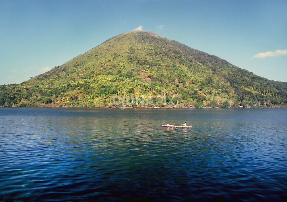 Fisherman paddles canoe in front of Gunung Api, Banda, Maluku, Indonesia