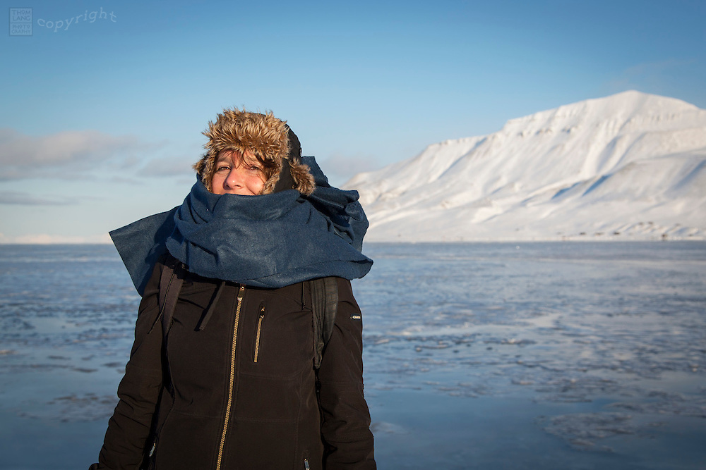 One woman bundled up at waters edge in freezing climate