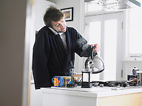 Man standing in kitchen using phone pouring water into coffee plunger