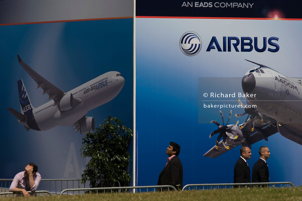 Delegates walk past a billboard of A380 airliner and military A400M transporter outside an EADS chalet at the Farnborough Air Show