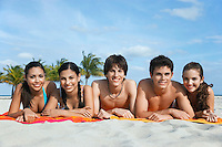 Group of teenagers (16-17) lying in row on beach towels portrait