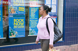 Woman out shopping dreaming of a holiday,