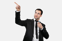 Young Caucasian businessman pointing upwards against white background