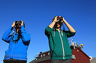 Grad students with binoculars observe Arctic terns (Sterna paradisaea) returning from Antarctica to Spitsbergen island on 80,000-killometer journey; Ny-Alesund, Kongsfjorden, Svalbard.