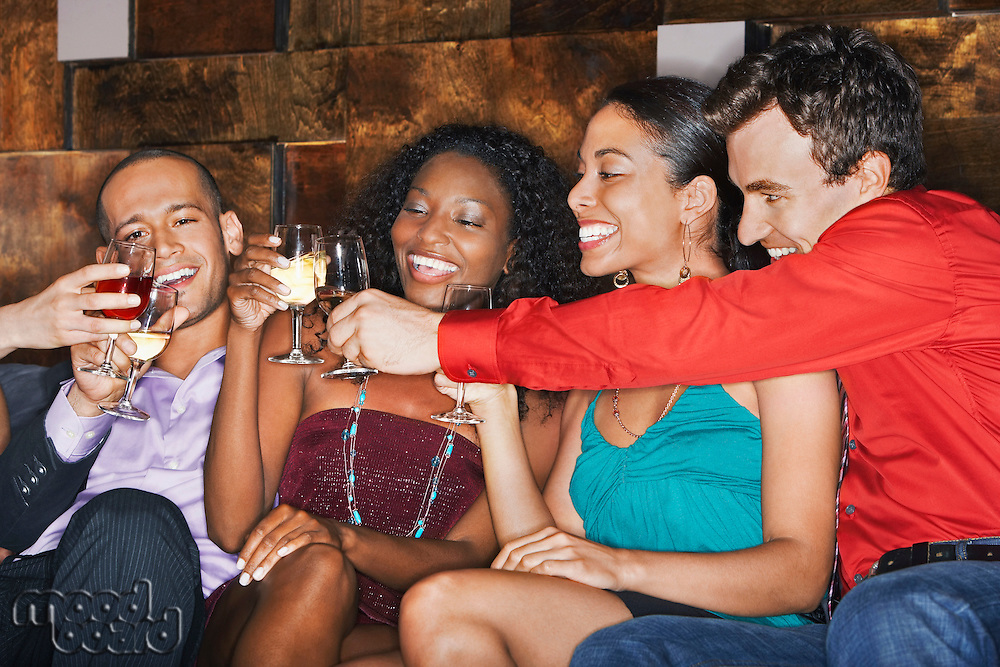 Group of friends toasting sitting in bar