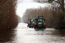 © London News Pictures. 31/01/2014. Burrowbridge, UK. Tractors plough through flood water near the village of Burrowbridge in Somerset on the Somerset levels.  The area has been hit severely by recent flooding which is forecast to get worse over the weekend . Photo credit: Jason Bryant/LNP