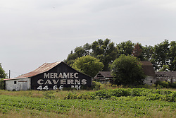 old derelict and abandoned barn, house and farmstead near Pontiac Illinois boasts the historic Route 66 Meramec Caverns advertising sign painted on the side of the falling down building.