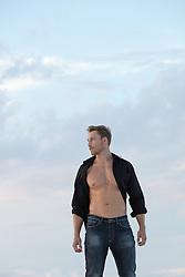handsome man with an open shirt outdoors