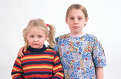 Portrait of two young girls; older girl with arm around younger girl,