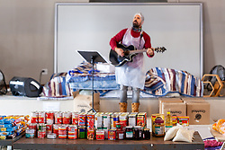 A pastor worships as volunteers prepare food parcels at a church, to be distributed to Vanwyk'svlei in Wellington, Western Cape, South Africa.(Picture: JULIAN GOLDSWAIN)
