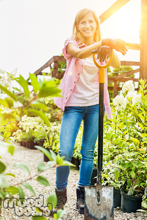 Portrait of mature female gardener holding shovel