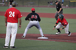 14 August 2015: Santiago Chirino dives bad to first base covered by Jimmy Yezzo during a Frontier League Baseball game between the Washington Wild Things and the Normal CornBelters at Corn Crib Stadium on the campus of Heartland Community College in Normal Illinois
