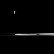 Saturn's rings lie between a pair of moons in this Cassini spacecraft view that features Mimas and Prometheus.