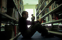 Male student studying in university library.