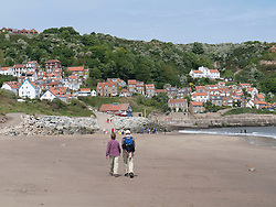 Walkers on the beach at Runswick Bay, Yorkshire
