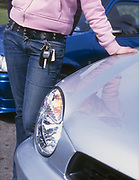 A girl standing next to her car, with her keys hanging out of her pocket, UK, 2000's