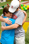 Friends embrace after award ceremony. Special Olympics U of M Bierman Athletic Complex. Minneapolis Minnesota USA