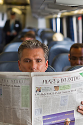 man reading a newspaper on a train