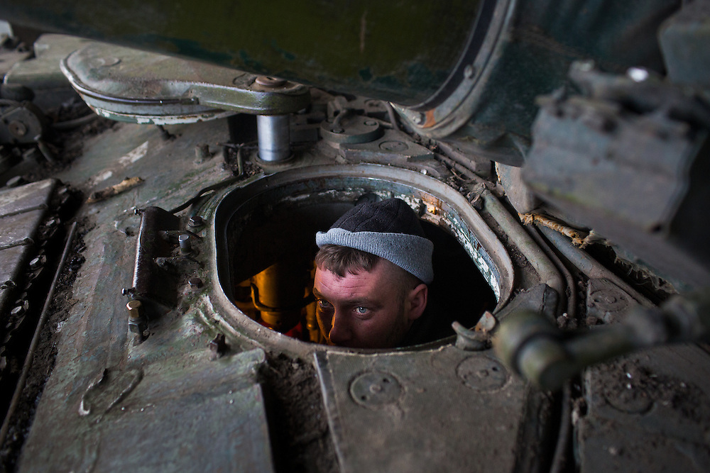 A volunteer with Dnipro-1 battalion does maintenance work on a tank on February 16, 2015 in Pisky, Ukraine.